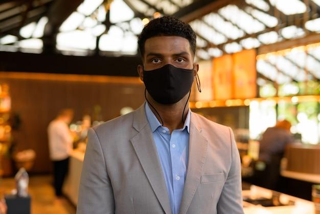 Portret przystojnego młodego afrykańskiego biznesmena noszącego garnitur i maskę na twarz