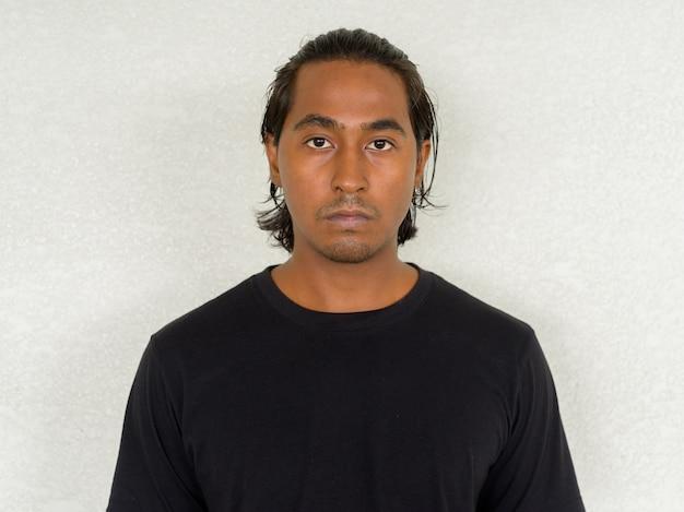 Portret przystojnego młodego indyjskiego mężczyzny na prostym tle