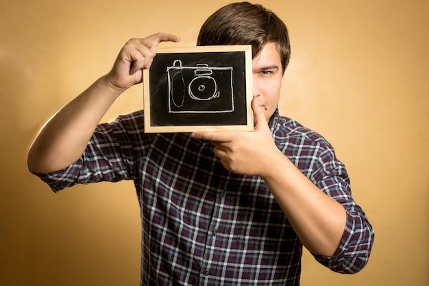 Portret przystojnego młodego mężczyzny trzymającego aparat narysowany na małej tablicy