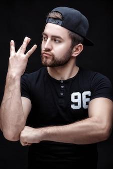 Portret przystojnego młodego mężczyzny w czarnej koszuli i czapce na czarnym tle rapera