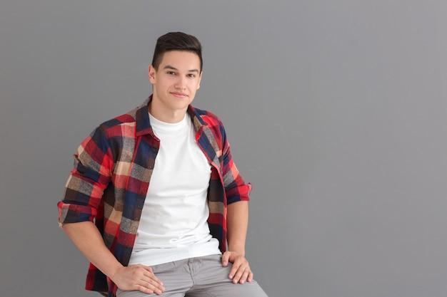 Portret przystojnego młodego mężczyzny w ubraniu na szaro
