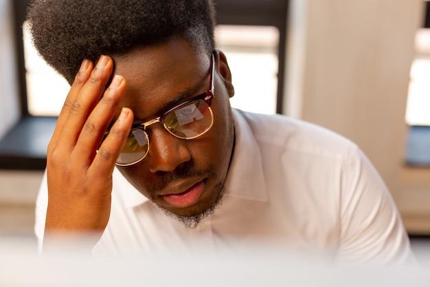 Portret przystojnego młodego mężczyzny wyglądającego poważnie podczas wykonywania swojej pracy