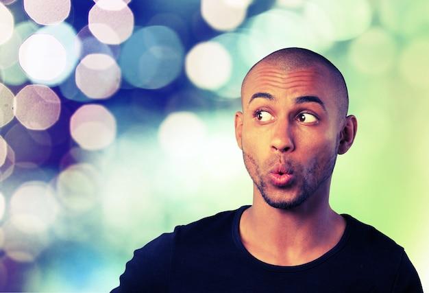 Portret przystojnego młodego mężczyzny z wyrazem twarzy na abstrakcyjnym tle światła