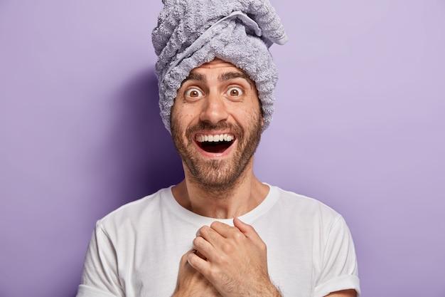Portret przystojnego młodzieńca o radosnym wyrazie twarzy, tuż po prysznicu nosi ręcznik, zaskoczony, że ma miękką skórę, ubrany w zwykłą białą koszulkę