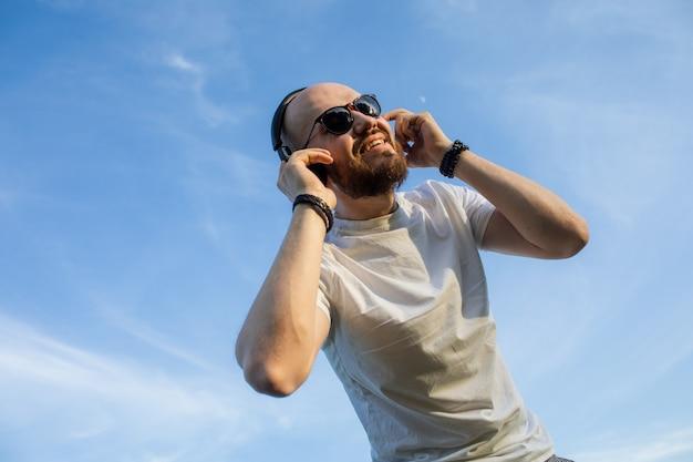 Portret przystojnego młodzieńca z brodą słuchającego muzyki w słuchawkach na tle zachmurzonego nieba bac...