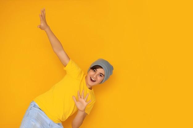 Portret przystojnego nastolatka w wieku 12-13 lat na żółtym tle.