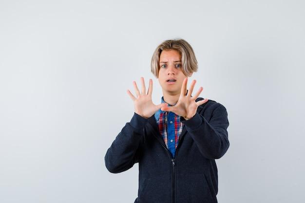 Portret przystojnego nastoletniego chłopca pokazujący gest kapitulacji w koszuli, bluzie z kapturem i patrząc przestraszony widok z przodu