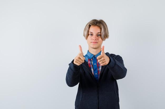 Portret przystojnego nastoletniego chłopca pokazujący podwójne kciuki w koszuli, bluzie z kapturem i patrzący wesoły widok z przodu