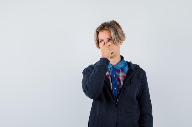 Portret przystojnego nastoletniego chłopca szczypie nos, wąchając coś obrzydliwego w koszuli, bluzie z kapturem i patrząc niezadowolony widok z przodu