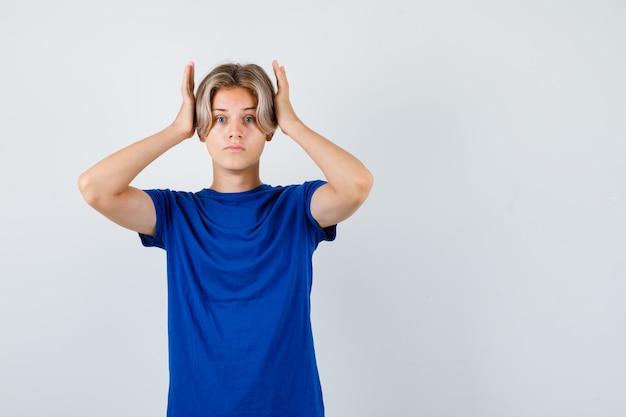 Portret przystojnego nastoletniego chłopca trzymającego ręce na głowie w niebieskiej koszulce i patrzącego na wzburzony widok z przodu