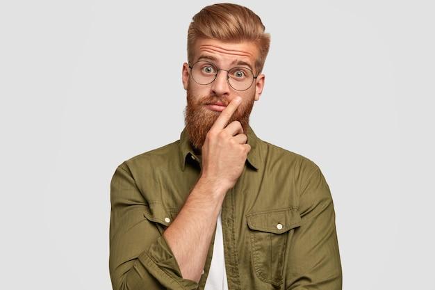 Portret przystojnego niezdecydowanego mężczyzny z gęstą rudą brodą, wygląda zaskakująco, zastanawia się nad najnowszymi wiadomościami, ubrany w modne ciuchy, odizolowany na białej ścianie. wyrazy twarzy