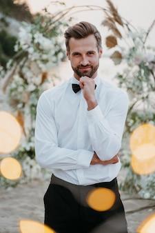 Portret przystojnego pana młodego na ślubie na plaży beach