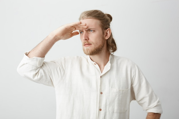 Portret przystojnego, pewnego siebie brodatego mężczyzny o blond włosach, trzymającego rękę na czole, jakby patrzył w dal jak marynarz lub kapitan