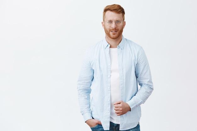 Portret przystojnego, pewnego siebie, odnoszącego sukcesy rudego przedsiębiorcy w koszuli i okularach, trzymającego kołnierz i uśmiechającego się z uroczym i zalotnym wyrazem twarzy na szarej ścianie