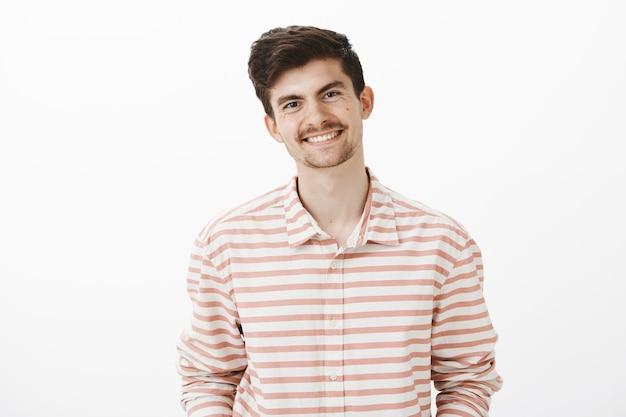 Portret przystojnego, przyjaznego modela z brodą i wąsami, szeroko uśmiechającego się podczas rozmowy ze współpracownikiem, omawiającego najnowsze wiadomości i wydarzenia w biurze