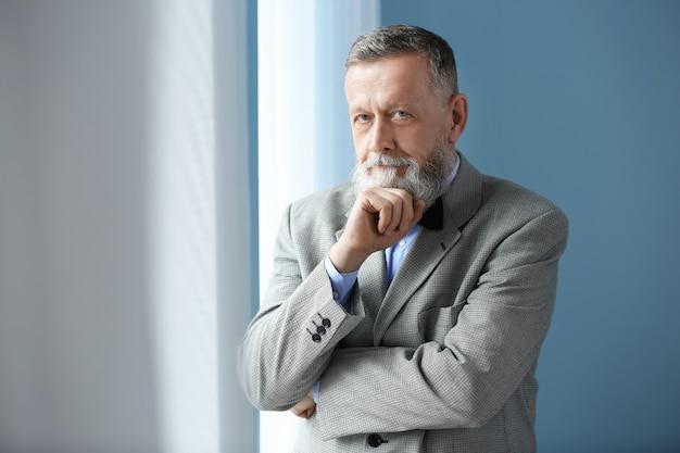 Portret przystojnego starszego mężczyzny w pobliżu okna w domu