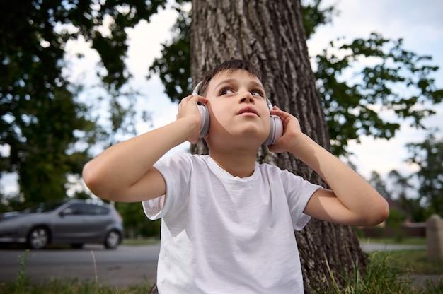 Portret przystojnego uroczego chłopca, noszącego słuchawki bezprzewodowe i cieszącego się słuchaniem muzyki, odpoczywającego podczas rekreacji między zajęciami w publicznym parku miejskim, po pierwszym dniu w szkole