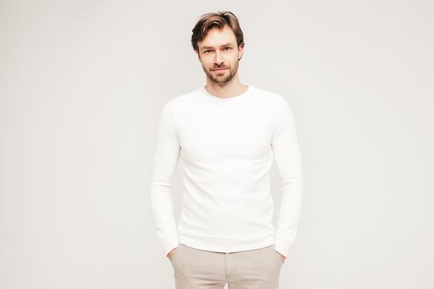 Portret przystojnego uśmiechniętego hipstera drwala modelu biznesmena noszącego dorywczo biały sweter i spodnie