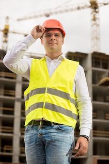 Portret przystojnego uśmiechniętego inżyniera w kasku pozowanie przed pracującym dźwigiem budowlanym
