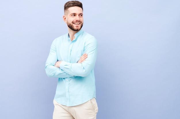 Portret przystojnego uśmiechniętego młodego mężczyzny w casualowej koszuli i spodniach