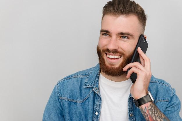 Portret przystojnego uśmiechniętego młodego mężczyzny w zwykłych ubraniach, stojącego na białym tle nad szarą ścianą, rozmawiającego przez telefon komórkowy