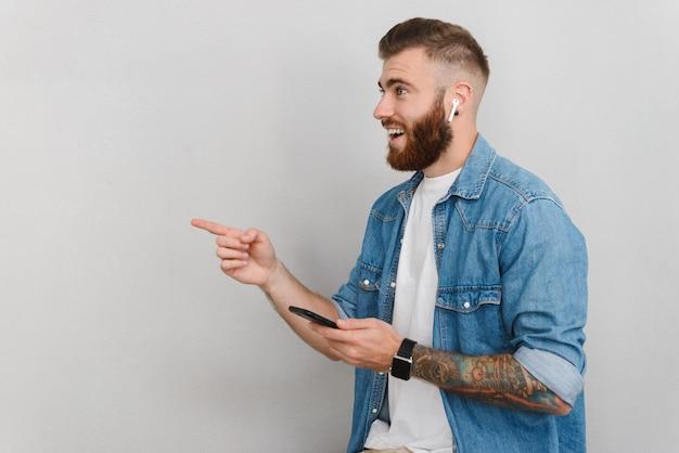 Portret przystojnego uśmiechniętego młodego mężczyzny w zwykłych ubraniach, stojącego na białym tle nad szarą ścianą, słuchającego muzyki przez bezprzewodowe słuchawki, wskazującego palcem