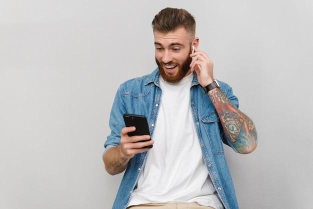 Portret przystojnego uśmiechniętego młodego mężczyzny w zwykłych ubraniach, stojącego na białym tle nad szarą ścianą, słuchającego muzyki za pomocą bezprzewodowych słuchawek, trzymającego telefon komórkowy