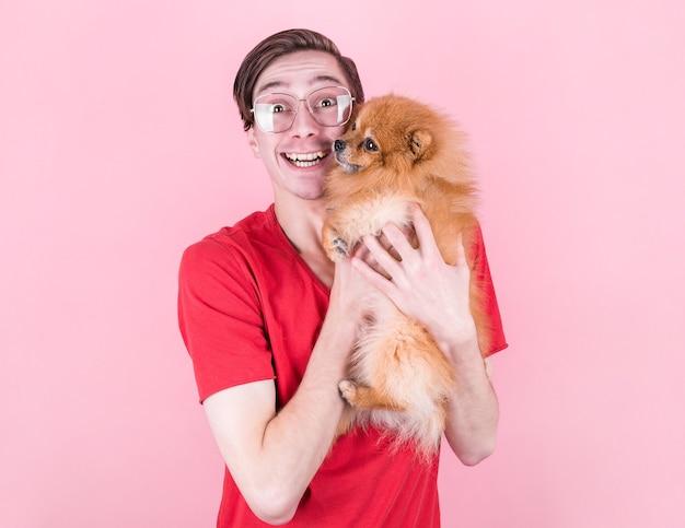 Portret przystojnego, wesołego mężczyzny, nosi okulary, czerwoną koszulkę, trzyma pomeranię, ma radosny wyraz twarzy, pozuje z pustą przestrzenią na kopię. zwierzęta i przyjaźń
