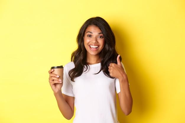 Portret przystojnej afroamerykańskiej dziewczyny, pokazującej kciuk w górę i pijącej kawę, stojącej zadowolonej na żółtym tle
