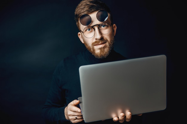 Portret przystojnej brunetki brodaty mężczyzna pracuje w biurze używać srebnego laptop odizolowywającego nad zmrok ścianą