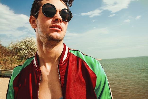 Portret przystojni mężczyzna w okularach przeciwsłonecznych na dennym tle