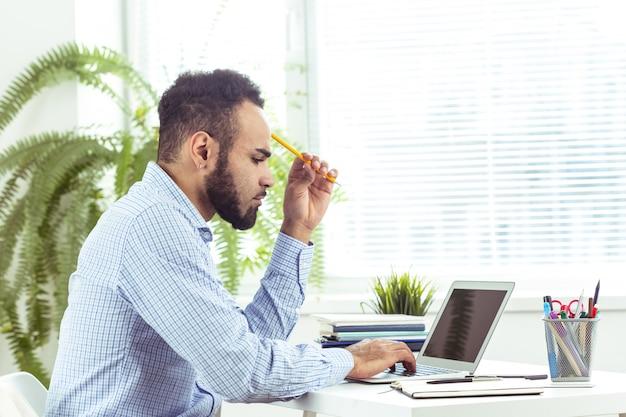 Portret przystojny afrykański czarny młody biznesowy mężczyzna pracuje na laptopie przy biurem