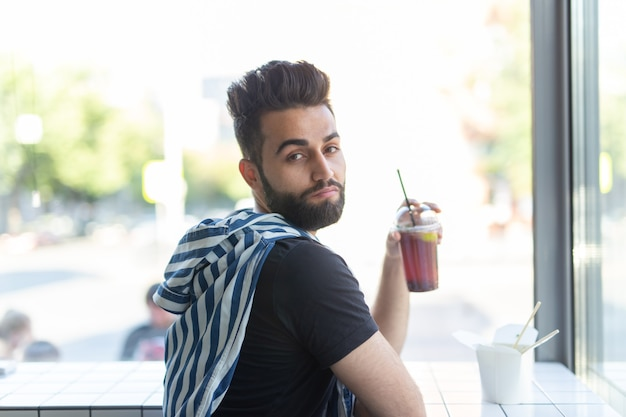 Portret przystojny arabski mężczyzna picia koktajl w kawiarni. pojęcie odpoczynku i przerwy.