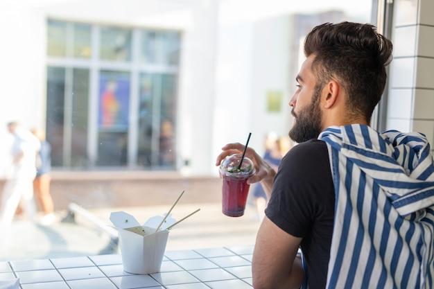 Portret przystojny arabski mężczyzna picia koktajl w kawiarni. pojęcie zdrowych napojów i stylu życia.