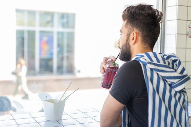 Portret przystojny arabski mężczyzna pije smoothie w kawiarni koncepcja zdrowych napojów i