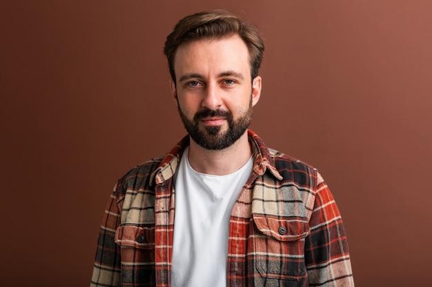 Portret przystojny atrakcyjny stylowy brodaty mężczyzna na brązowym