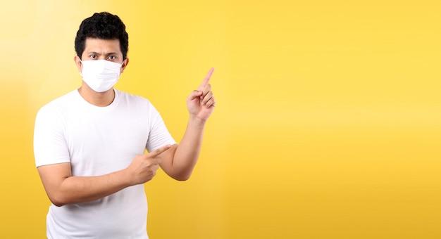 Portret przystojny azjatycki mężczyzna jest ubranym maskę jest chory wskazujący palec odizolowywający