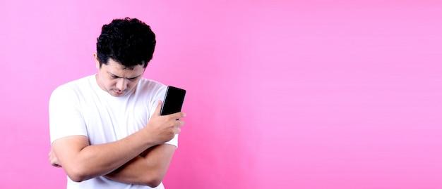 Portret przystojny azjatycki mężczyzna z marzycielskim spojrzeniem, myśleć podczas gdy trzymający smartphone, na menchii ścianie.