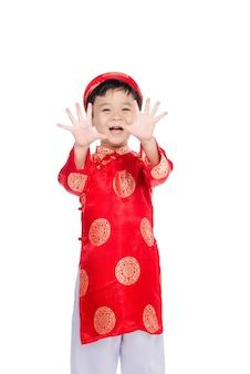 Portret przystojny azjatyckiego chłopca na tradycyjny strój festiwalowy. ładny mały wietnamski chłopiec w sukience ao dai uśmiechający się.