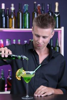 Portret przystojny barman przygotowuje koktajl, w barze
