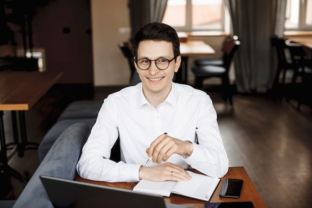 Portret przystojny biznesmen kaukaski siedzi przy biurku i uśmiecha się, mając na sobie okulary ubrane na biało.