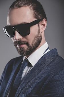 Portret przystojny biznesmen modelka ubrana w elegancki niebieski garnitur z okularami przeciwsłonecznymi