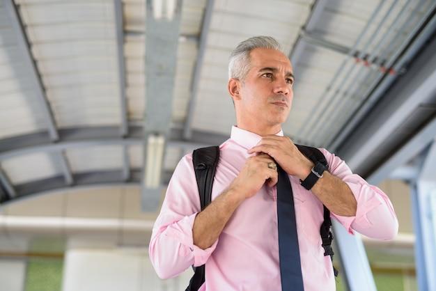Portret przystojny biznesmen perski z siwymi włosami przy kładce dla pieszych w mieście