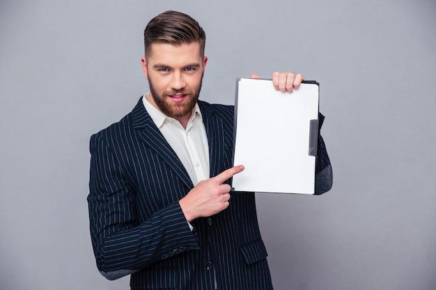 Portret przystojny biznesmen pokazując pusty schowek na szarej ścianie