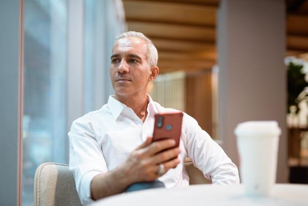 Portret przystojny biznesmen siedzi w kawiarni i korzysta z telefonu komórkowego, patrząc przez okno poziome ujęcie