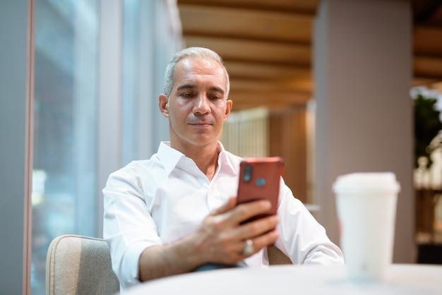 Portret przystojny biznesmen siedzi w kawiarni i korzysta z telefonu komórkowego