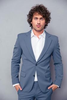 Portret przystojny biznesmen, stojąc na szarej ścianie i patrząc z przodu