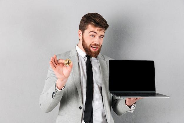 Portret przystojny biznesmen trzyma bitcoin