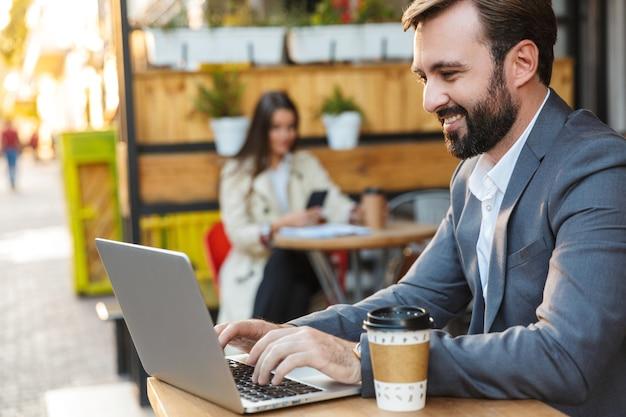 Portret przystojny biznesmen w formalnym garniturze, uśmiechając się i pracując na laptopie, siedząc w kawiarni na świeżym powietrzu