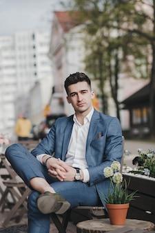 Portret przystojny biznesmen w garniturze siedzi na ulicy
